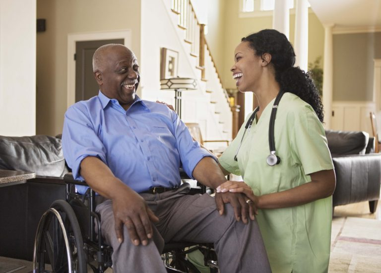 Nurse with man in wheelchair at home